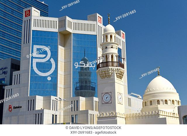 The unique clock tower minaret in the new Al Yateem Mosque in Manama, Bahrain stands before the Batelco telecoms offices