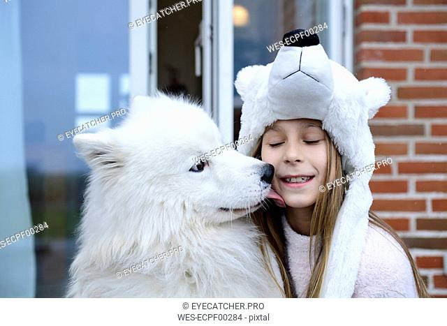 Portrait of girl on terrace with her white dog