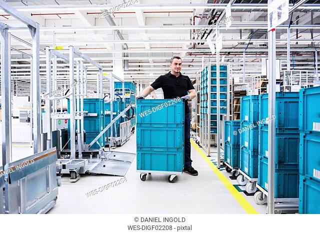 Man at tugger train organising boxes in industrial hall