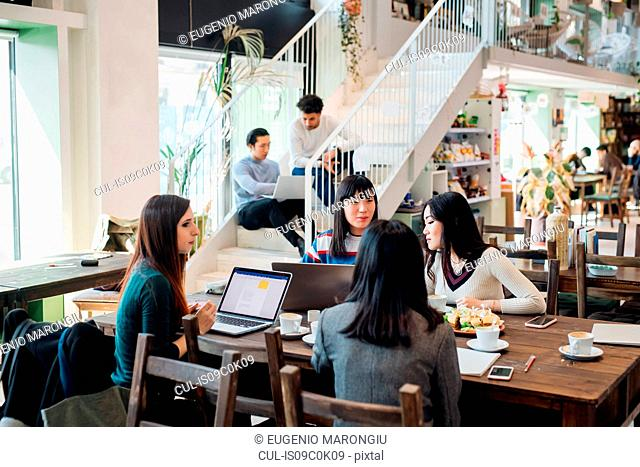Young businesswomen remote working having meeting at cafe table