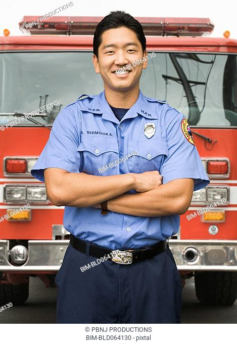 Asian firefighter next to fire truck