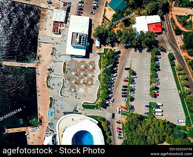 The top view on the picturesque embankment of the bay. Cars parked in the parking lot