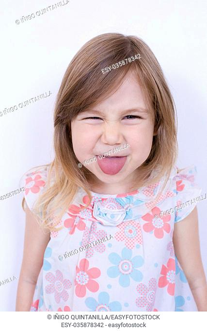 portrait of three years old blonde girl, with white dress with red and blue flowers looking with funny expression sticking out tongue