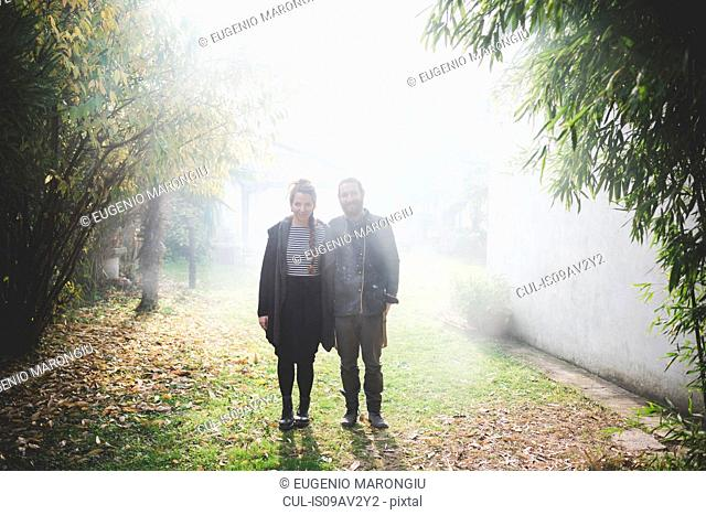 Full length front view of couple standing in misty garden looking at camera smiling