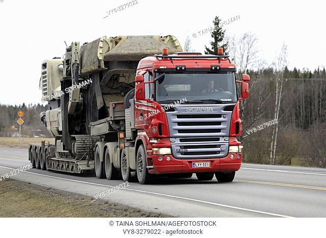 Forssa, Finland - March 30, 2019: Red Scania R620 semi of Veljekset Makitalo Oy pulls Metso Lokotrack crusher on low loader trailer along highway