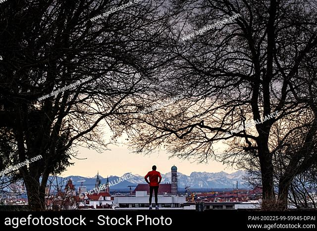 25 February 2020, Bavaria, Munich: A jogger stands on Luitpold Hill in the Schwabing district and looks over the backdrop of the Bavarian capital