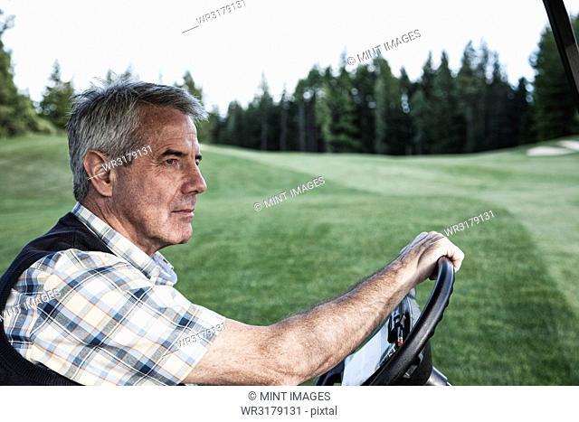 Senior golfer driving a golf cart on the cart path of a golf course