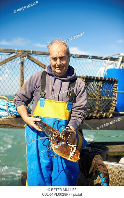 Fisherman holding lobster on boat
