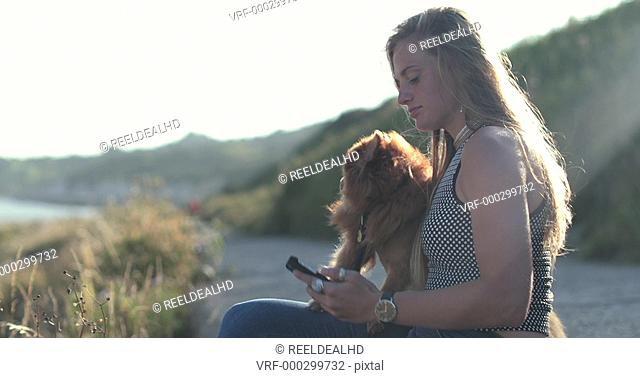 Young adult female taking selfie with dog