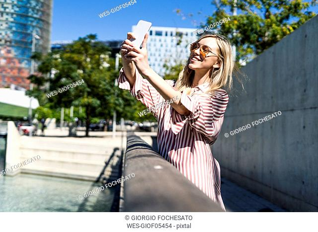 Spain, Barcelona, smiling young woman taking selfie with cell phone