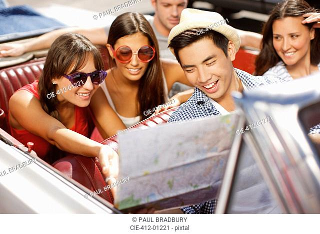 Friends reading road map in convertible