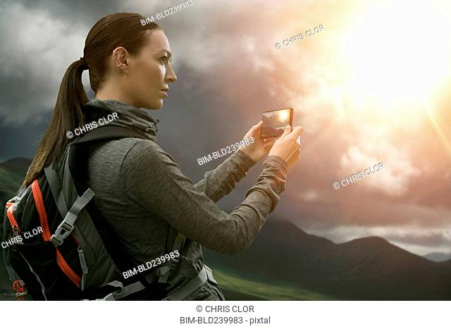 Caucasian woman photographing mountain landscape with cell phone
