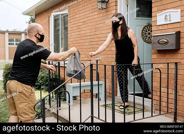 Woman taking plastic bag from delivery man with protective mask