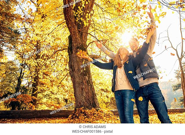 Happy couple having fun in autumn in a forest