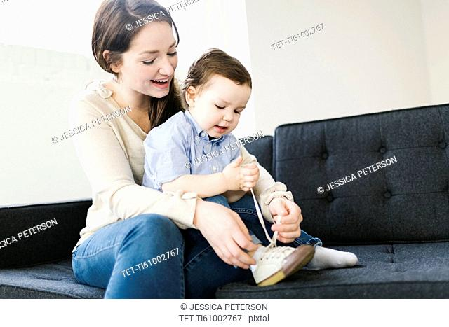 Mother tying son's (4-5) shoe