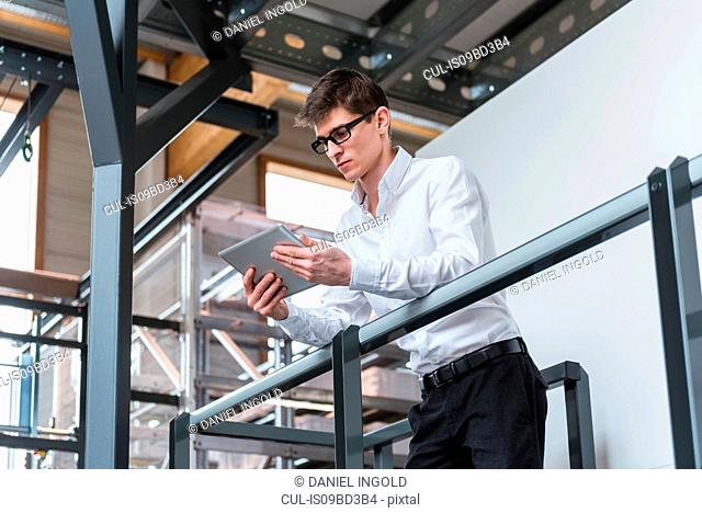 Young man standing in factory, leaning on railing, using digital tablet, low angle view