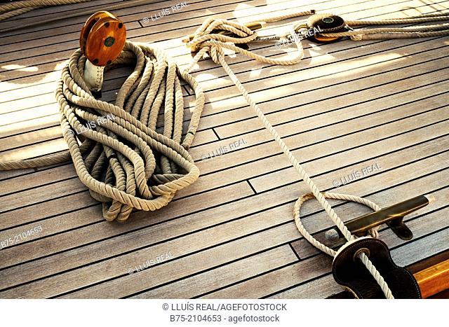 Wooden deck of a classic sailboat, pulleys and several ropes moored in Port Mahon, Menorca, Balearic Islands, Spain
