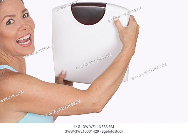 Portrait of a woman holding a bathroom scale and laughing