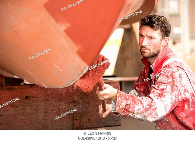 Male ship painter roller painting ship hull red in ship painters yard