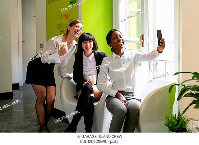 Three female business creatives taking a break and taking smartphone selfie in office