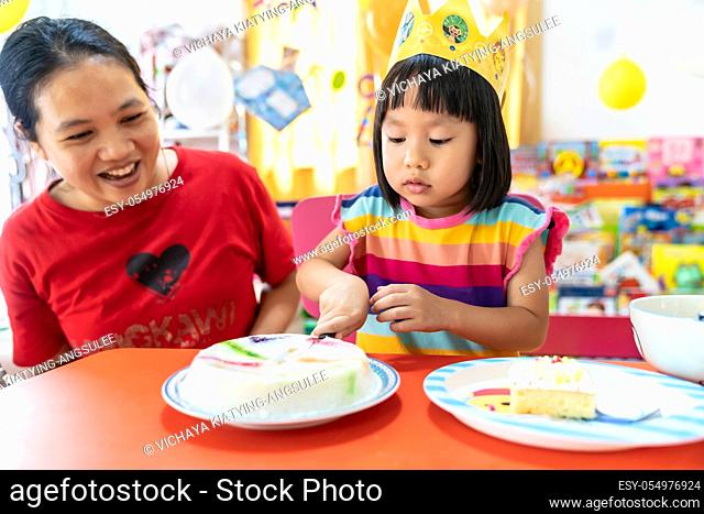 Asian girl kid cutting her birthday cake celebrate with mom alone because city lockdown while COVID-19 Pandemic. Celbration and quarantine concept