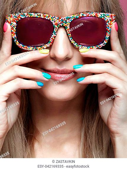 Young blonde smiling woman with fun candy glasses and varicoloured finger nails manicure on pink background