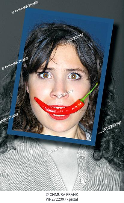 young woman holding chili in her mouth, face framed