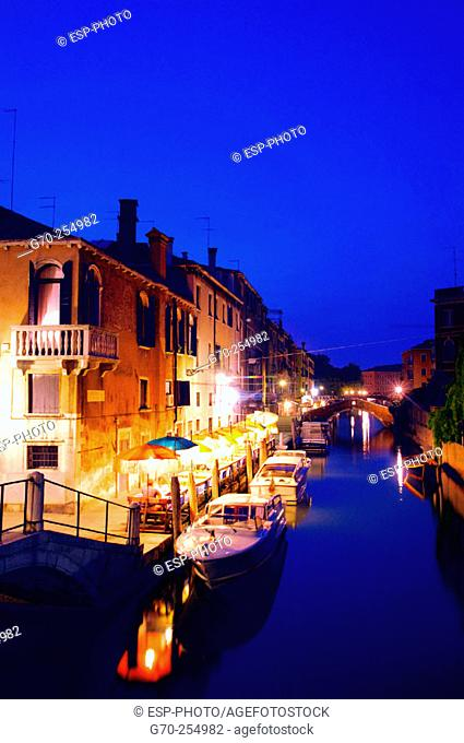 Restaurant on canal at dusk. Venice. Italy