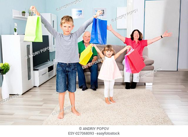 Happy Child Holding Shopping Bags In Front Of Family