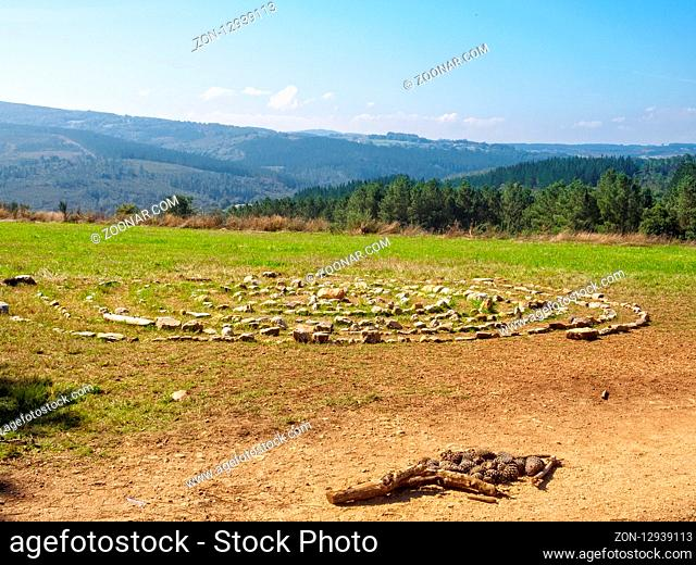 Beautiful Galician countryside, stone circles and a Camino waymark made of pine cones and pieces of wood - Portomarin, Galicia, Spain