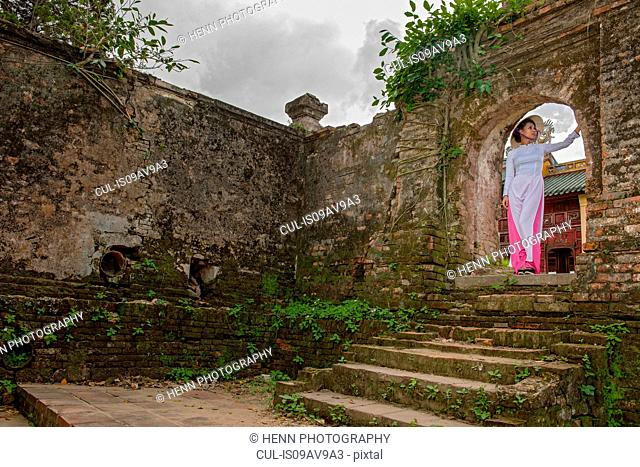 Low angle view of mid adult woman wearing ao dai dress and conical hat, standing in archway looking away, Hue, Vietnam