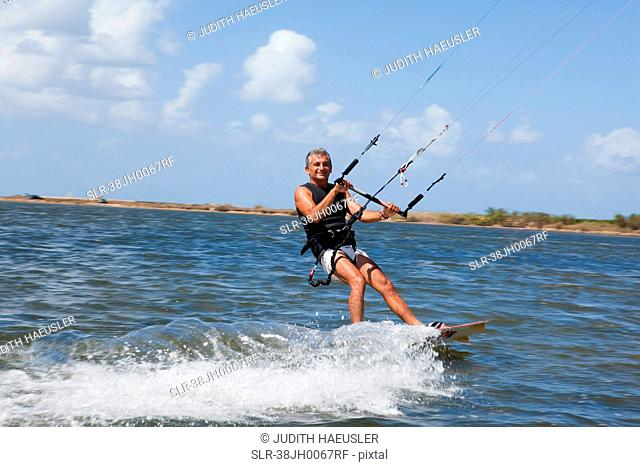 Older man wind surfing on lake