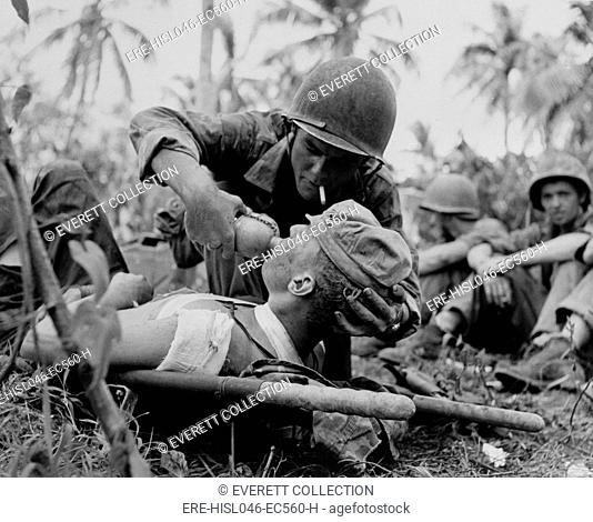 US Navy corpsman gives a drink to wounded Marine on Guam, July 1944, during World War 2. (BSLOC-2017-20-187)