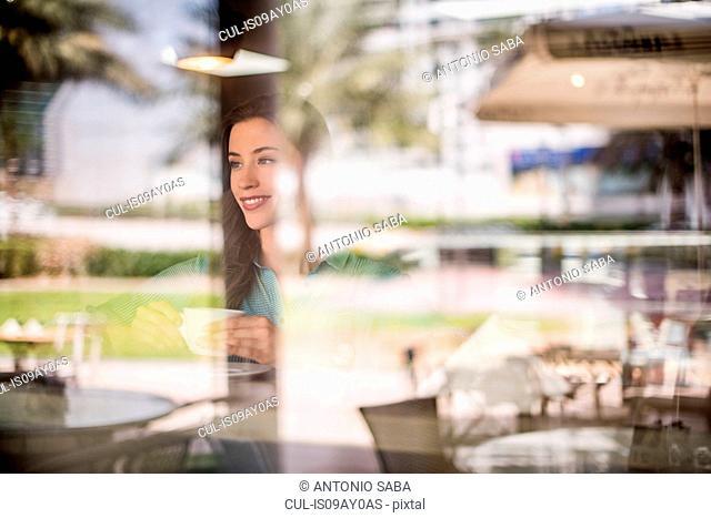 Happy woman behind reflective cafe window, Dubai, United Arab Emirates