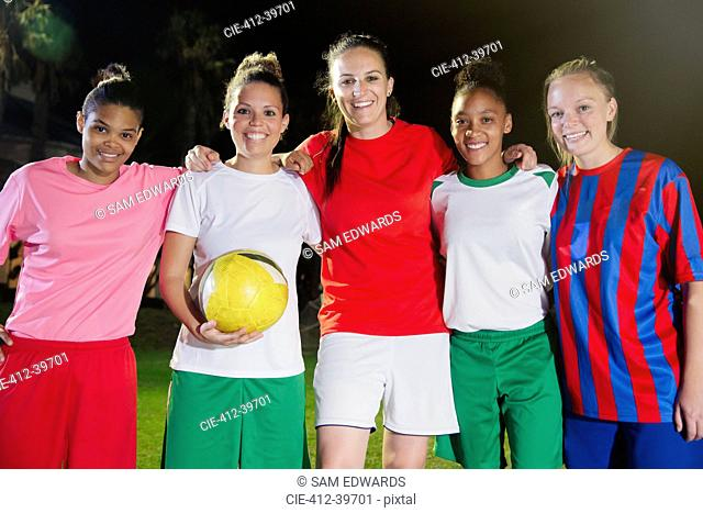 Portrait smiling, confident young female soccer team with ball