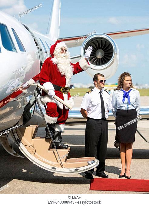 Full length of Santa waving hand on ladder of private jet
