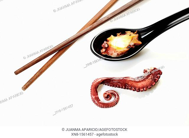 Boiled octopus tentacle, grilled octopus on spoon black color with chopsticks on white background