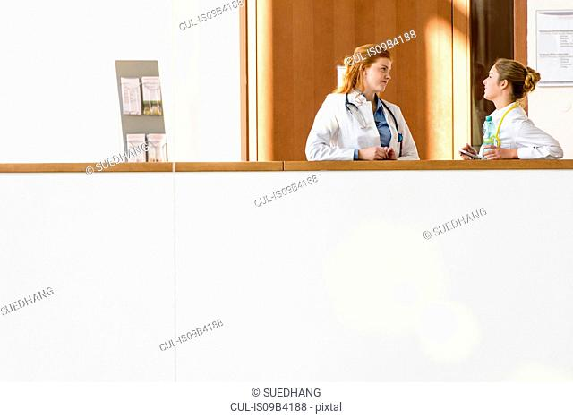 Two young female doctors leaning against hospital balcony talking