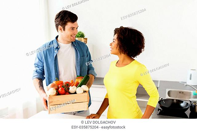happy couple with healthy food at home kitchen