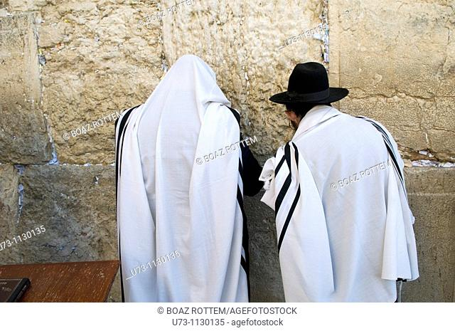 Jewish men pray by the wailing ( western ) wall of the old temple in Jerusalem
