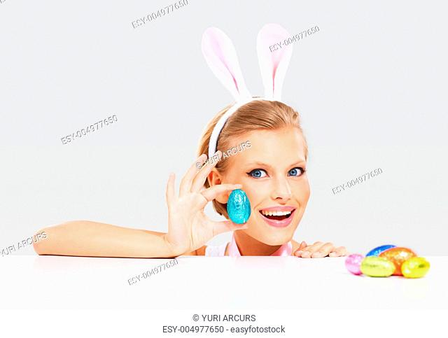 Happy young woman wearing bunny ears and holding up a colorful Easter egg