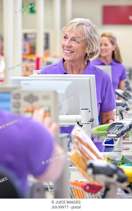 Portrait Of Cashier At Supermarket Checkout