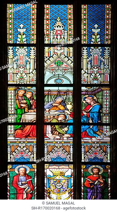 Stained Glass Window depicting Sinful Woman Washing Jesus Feet. Below is a scene of St Bartholomew and St Matthew flanking a crest