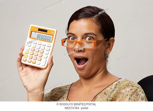 Woman in her 30s with retro sunglasses shows an 8 million figure on her calculator