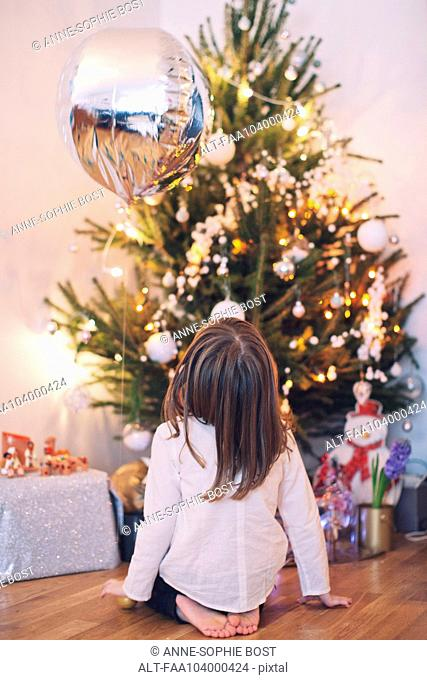 Girl sitting on floor gazing up at Christmas tree