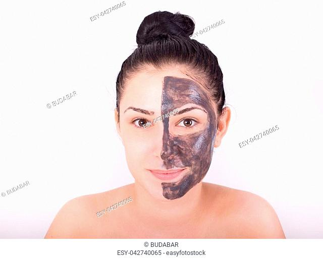 Young pretty woman with clay mask on half face. Skin care and beauty concept