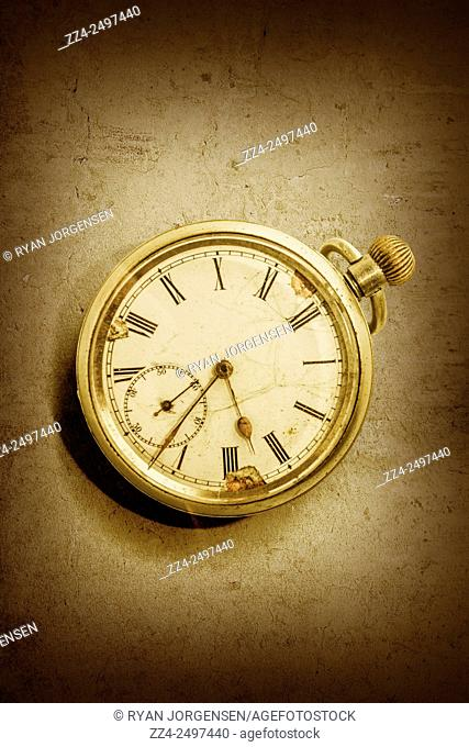 Classical style still life photograph on a vintage gold pocket watch on textured surface. Timeless