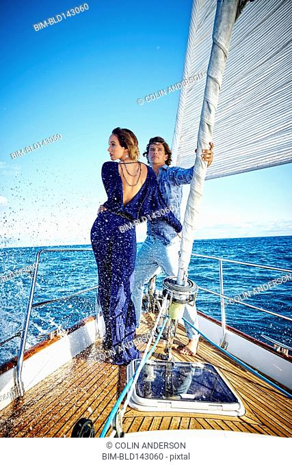Glamorous couple standing on yacht deck