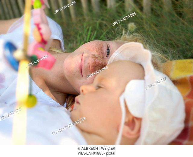 Smiling girl lying with baby girl on blanket on a meadow