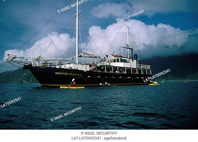 Coast. Deep fjord,inlet. Milford Wanderer passenger ship. Yellow kayaks,canoes. People